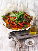 Pumpkin spaghetti pizza topped with fresh rocket