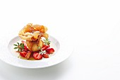 A quark-filled strudel pastry pocket on a bed of rhubarb and strawberries in woodruff jus