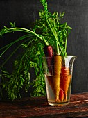Various carrots in a glass of water