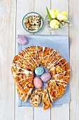 An Austrian yeast ring decorated with colorful eggs, quail eggs and tulips