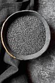 Schwarzer Sesam in schwarzer Schale (Aufsicht)