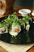 Sushi rolls with salmon, avocado, fresh cheese and green coloured fish roe