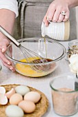 A woman is pouring maple syrup into an egg mixture as prep for a muffin mix