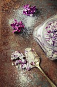Glass jar with lilac flowers in sugar withfresh flowers and vintage spoon
