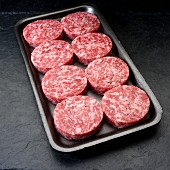 Uncooked breakfast pork sausage patties in plastic tray