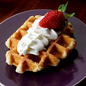 Belgian waffle with whipped cream and one strawberry