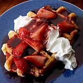 Belgian waffle with whipped cream and strawberry compote