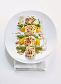 Scallops in a sesame coating with green asparagus and oranges