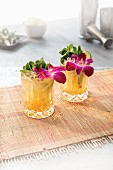 Two Mai Tai cocktails garnished with orchid blossoms and mint in crystal glasses