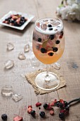 White Sangria with berries in a large wine glass and ice