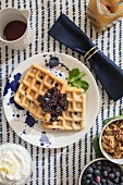 Zitronenwaffeln mit Blaubeeren auf gedeckten Tisch (Aufsicht)