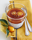 Panna cotta in a glass with poppyseeds, orange jelly and candied kumquats