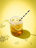 Elderberry and apple juice in a glass with a straw against a yellow background