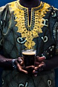 A Senegalese man in a traditional Boubou holds a glass of Touba (coffee drink, Senegal, Africa)