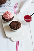 Chocolate and coffee muffins being decorated with strawberry frosting