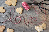 Heart shaped cookies and striped string spelling out the word 'love'