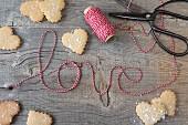 Herzplätzchen und Schriftzug Love aus gestreifter Schnur