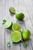 Fresh limes, whole and halved, on a wooden board