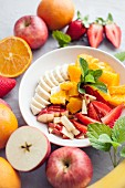 Fruit salad with oranges, bananas, apple and strawberries