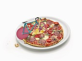 A bike-shaped pizza cutter on top of a salami pizza