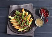 A superfood salad with avocado, papaya and pomegranate seeds