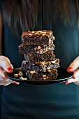 A woman holding a plate of gluten-free hazelnut brownies