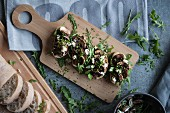 Bruschetta with mushrooms, feta and rocket on a wooden chopping board (seen from above)