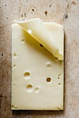 Slices of cheese with holes lying flat on a cream marble surface