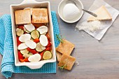 Toast and vegetables being layered into an ovenproof dish for vegetable gratin