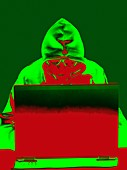 Hooded figure hacking laptop computer