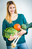 Woman holding vegetables in her arms