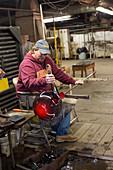 Glassblower shaping a glass vessel