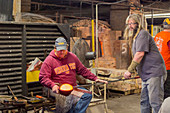 Glassblowers shaping a molten glass vessel