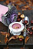 Red cabbage soup in a small soup terrine, with chestnuts and autumn leaves