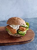 A fish finger sandwich with tartar sauce in a wholemeal bread roll