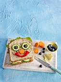 A healthy sandwich with vegetables in the shape of a face