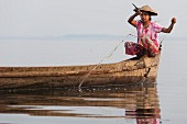 A young Asian woman fishing at Indawgyi Lake (Kachin, Myanmar, Burma)