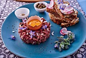 Beef tartare served with toasted bread and oyster plant flowers