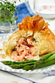Filo pastry parcels with salmon and prawn filling and green asparagus