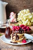 Gestapelte Pancakes mit Schokoladensauce und Himbeeren