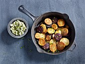 Fried potatoes and black pudding in a pan served with apple salad