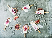 Blood orange, yogurt and granola popsicles on ice cubes over grey concrete background