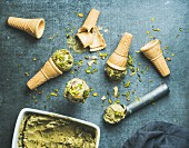 Homemade pistachio ice cream in ceramic mold and metal scooper with crashed pistachio nuts and waffle cones