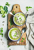 Spring detox broccoli green cream soup with mint and coconut cream in blue bowls on rustic wooden board