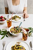 A woman is photographed at a tablesetting with tilapia and black bean salsa in her plate