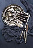 Old silver cutlery on a metal plate (top view)