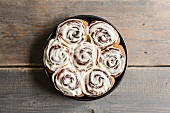 Cinnamon and cardomom buns in a pan with vanilla cream cheese frosting