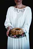 A woman holding a pear cake on a cake stand