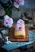 Mandelkuchen in Kastenform dekoriert mit violetten Blüten