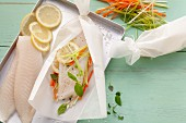 Ingredients for making fish fillets with vegetables wrapped in parchment paper